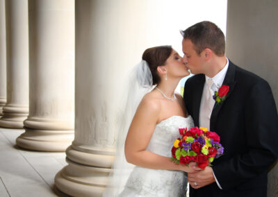 kissing.wedding.ceremony.pillars.bride.groom